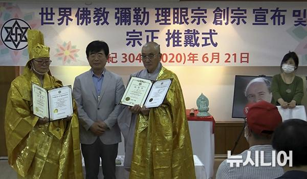 라엘리안 무브먼트 한국 정윤표 대표가 법조스님에게 불교대사, 춘해스님에게부대사를 임명하고 기념촬영하고 있다.